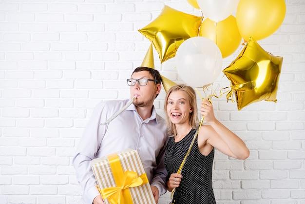 白いレンガの壁に金色の風船とギフトボックスを保持している誕生日パーティーを祝う幸せな笑いカップル