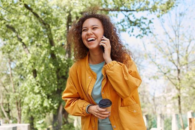幸せな笑い巻き毛のダークスキンの女の子、黄色のジャケットを着て、コーヒーを飲み、公園の天気を楽しんで、彼の友人と電話で話している。