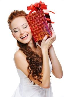 Счастливый смех милая девушка держит подарок закрывает голову над белой