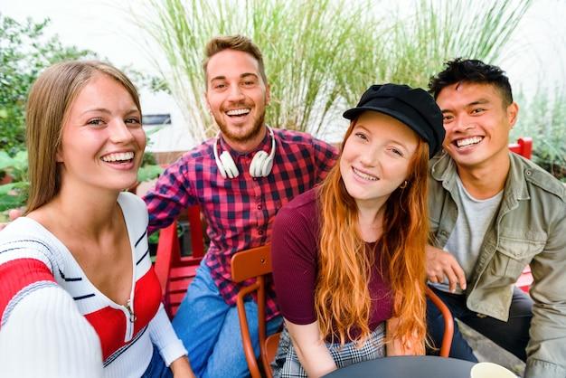 屋外パティオのテーブルの周りに集まって一緒に自分撮りをしている若い友人の多様なグループを笑って幸せ