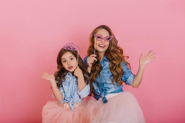幸せな笑っている女の子と女性がピンクの背景に驚いた表情と一緒に面白いポーズ。かわいいカーニバルマスクを着用し、手を振って彼女の小さな娘と遊ぶ素敵な若い母親