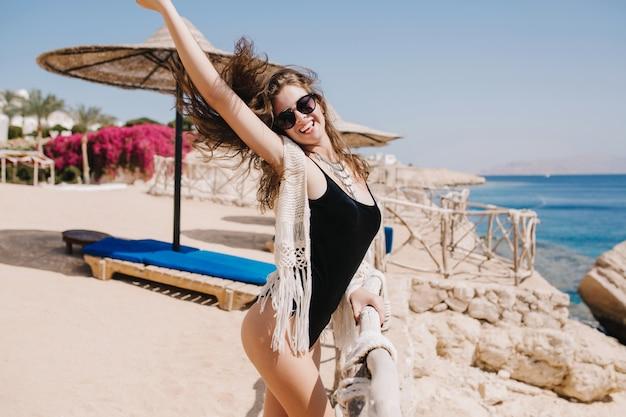 海リゾートで休暇を楽しんで手を振っている髪でポーズ黒い水着で幸せな笑っている女の子。夏の海の近くの砂浜で楽しんで陽気な若いブルネットの女性の肖像画