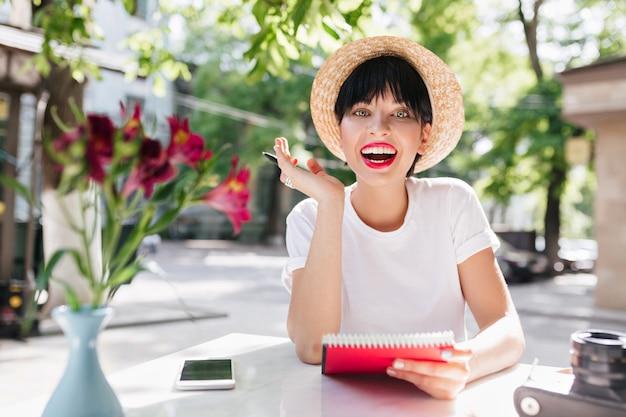 緑の庭でノートとペンを持って座って、短い黒髪の幸せな笑いの女の子は素晴らしいアイデアを持っていました