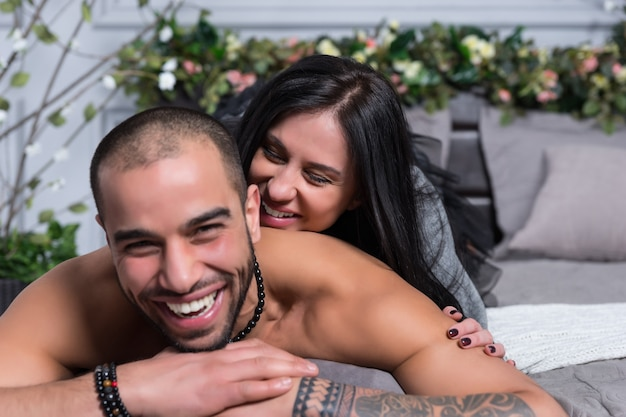 Happy laughing international couple of man with bare chest and with tattooed hands, brunette woman lying on him on the gray cozy bed in the bedroom
