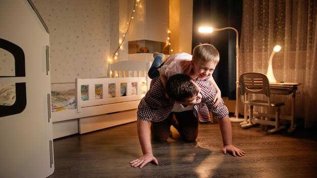 Счастливый смех маленький мальчик прыгает на спину отца и едет на нем. понятие о ребенке, играющем с родителями и семьей, вместе проводящим время в ночное время.