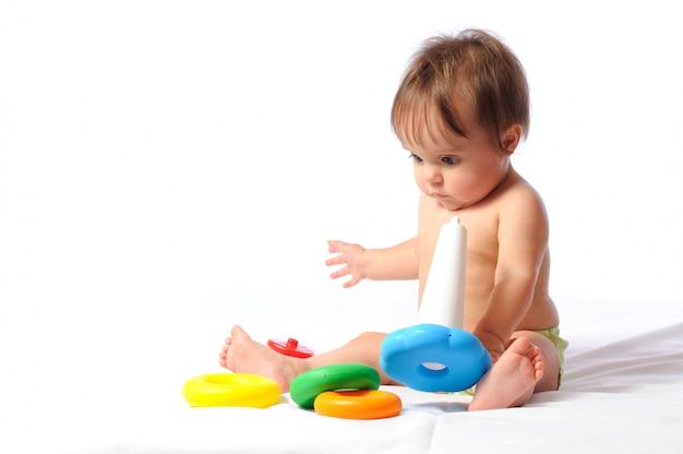 幸せな笑いの小さな子供が座って、愛するおもちゃで遊ぶ。