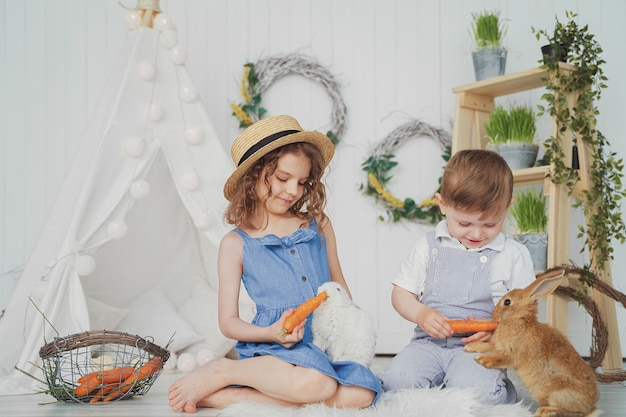 Happy laughing little girl and boy playing with a baby rabbit