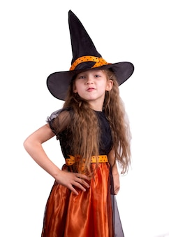 Happy laughing little girl wearing a witch carnival costume playing with a basket for treats. child girl halloween kid against a white background.