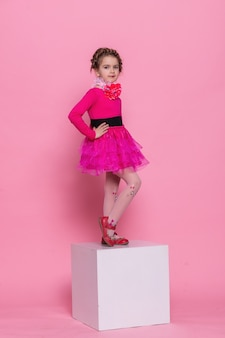 Счастливый смех маленькая девочка с длинными волосами, танцующая на розовом фоне. маленькая девочка на белом кубе на розовом фоне