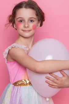 Счастливая смеющаяся маленькая девочка с длинными волосами танцует на розовом фоне