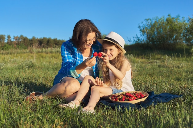 Happy laughing mother and child daughter together outdoors, sitting on green grass, picnic with bowl of fresh strawberries. mothers day, may nature
