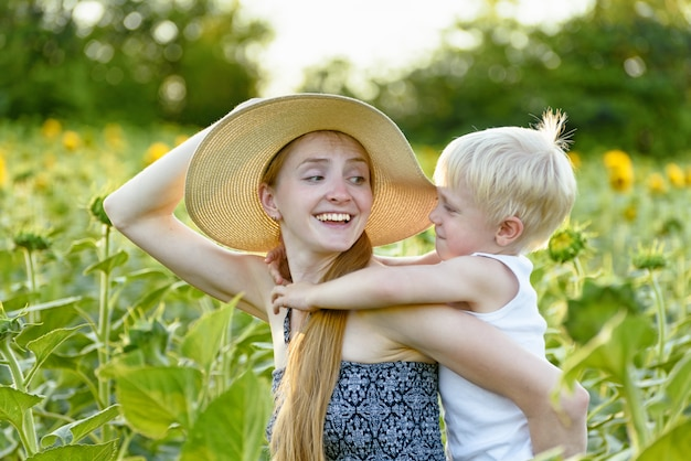 Happy laughing mother giving toddler son piggyback ride on green blooming sunflowers field