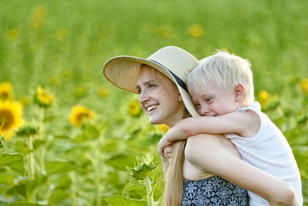 Happy laughing mother giving toddler son piggyback ride on wall of green blooming sunflowers field. close-up
