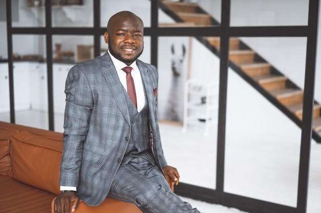 幸せな笑い金持ちのアフリカ系アメリカ人実業家の成功した大物は、スタイリッシュで高価なスーツを着て...
