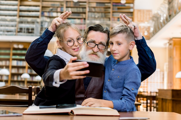 Happy laughing teen granddaughter with grandson making photo selfie with their elegant handsome old granddad with funny finger gestures, library interior on the background