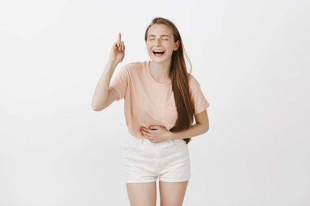 Счастливый смех девочка-подросток позирует у белой стены