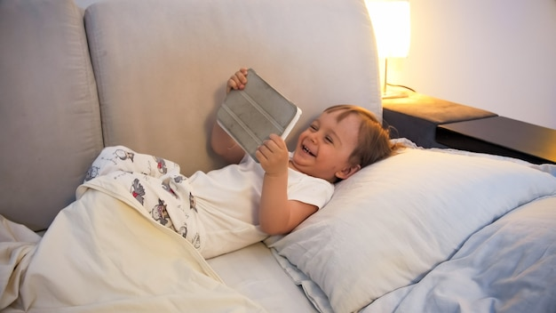 Happy laughing toddler boy lying in bed at night and watching cartoons on digital tablet computer.