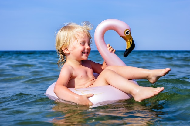 Happy laughing todler girl enjoying swimming in sea with rubber ring flamingo