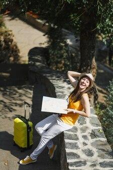 여행 가방 도시 지도가 야외 도시 공원의 돌 위에 앉아 있는 노란색 옷 모자를 쓴 행복한 웃고 있는 여행자 관광 여성. 주말 휴가를 여행하기 위해 해외로 여행하는 소녀. 관광 여행 라이프 스타일.