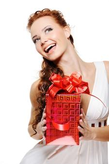 Felice donna che ride tenendo il presente e alzando lo sguardo su sfondo bianco