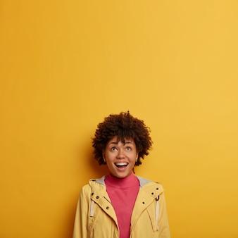 La donna che ride felice guarda sopra con interesse e gioia, controlla una pubblicità divertente, vestita con una giacca casual, ha i capelli ricci, posa contro lo spazio giallo