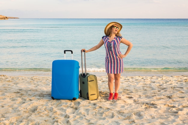 海の近くに立っているスーツケースと幸せな笑う女性観光客。旅行と夏休みの概念。