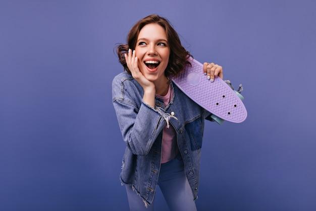 Счастливый смех женщина с волнистой прической, весело. крытый снимок очаровательной кудрявой девушки в джинсовой куртке, держащей лонгборд.