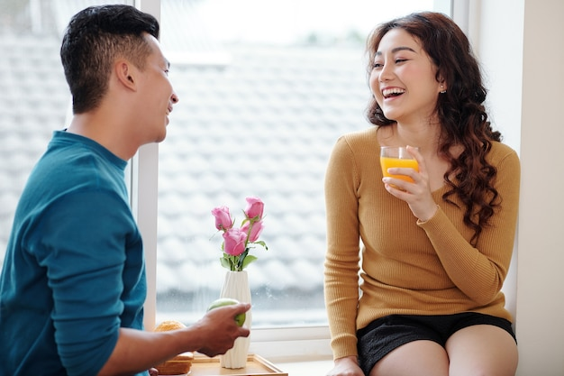 Happy laughing young asian woman sitting on window sill and enjoying having breakfast with boyfriend at home