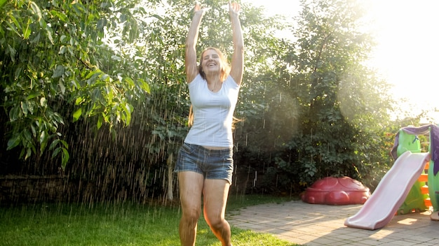 Happy laughing young woman dancing under rain at garden. girl playing and having fun outdoors at summer
