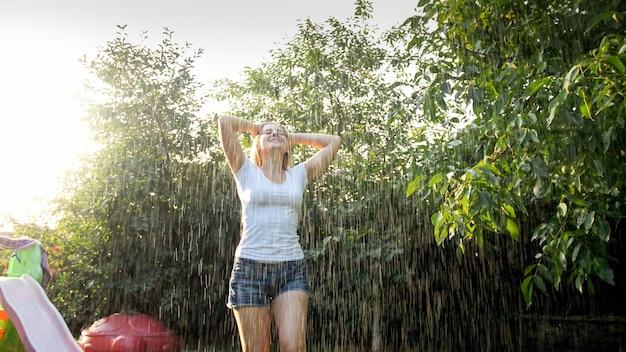 庭で雨の下で踊る幸せな笑い若い女性。夏に屋外で遊んで楽しんでいる女の子