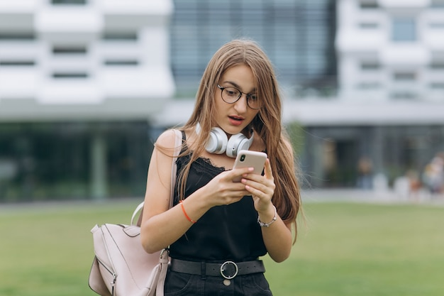 携帯電話アプリを使用して幸せな笑いの若い女性、楽しんで、良いニュース、ゲームをプレイ、魅力的な女性持株モバイルデバイス