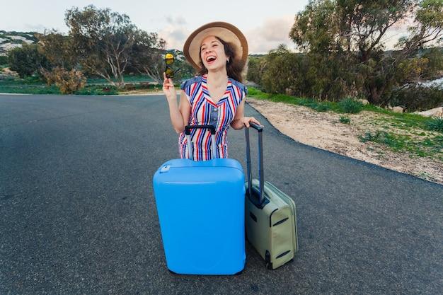 道路にスーツケースを持って幸せな笑いの若い女性。