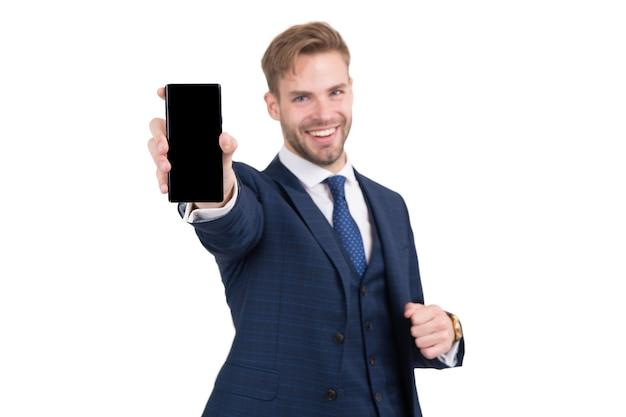 フォーマルなスタイルの幸せな弁護士は、白いスマートフォンで隔離された現代の電話モバイルデバイスを保持します。