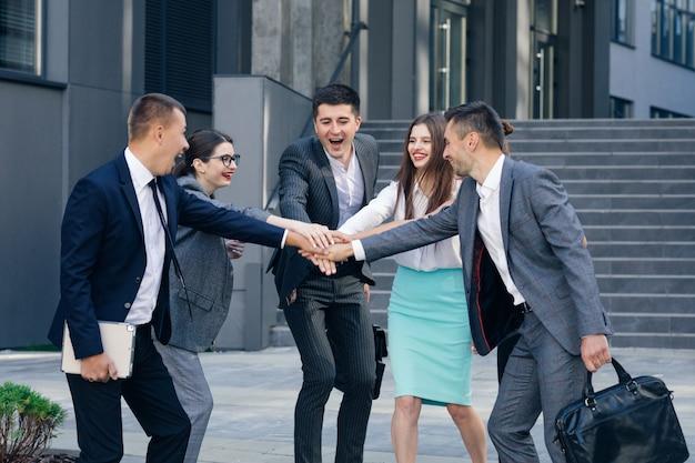 Счастливый лидер мотивирует разнообразных сотрудников. деловая команда дает пять вместе, группа офисных работников и тренер, участвующие в построении команды. отмечают успех. награда за хорошие результаты в концепции совместной работы.