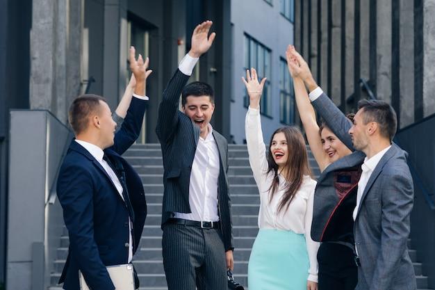 Счастливый лидер мотивирует разнообразных сотрудников. деловая команда дает пять вместе, группа офисных работников и тренер, участвующие в построении команды. отмечают успех. вознаграждение за хорошие результаты в концепции совместной работы.