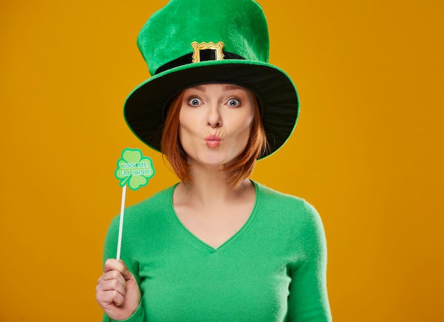 Happy leprechaun with green hat blowing a kiss