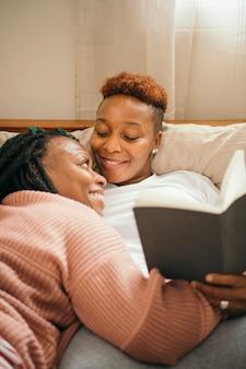 Счастливая пара лесбиянок обнимаются и вместе читают книгу