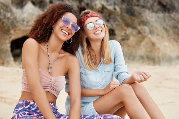 행복한 레즈비언 커플은 쾌활한 표정으로 사막에서 레크리에이션 시간을 즐기고 선글라스를 착용하고 절벽에 앉아 있습니다. 젊은 사랑스런 페미니스트들은 평온한 휴양지에서 공생을 즐긴다