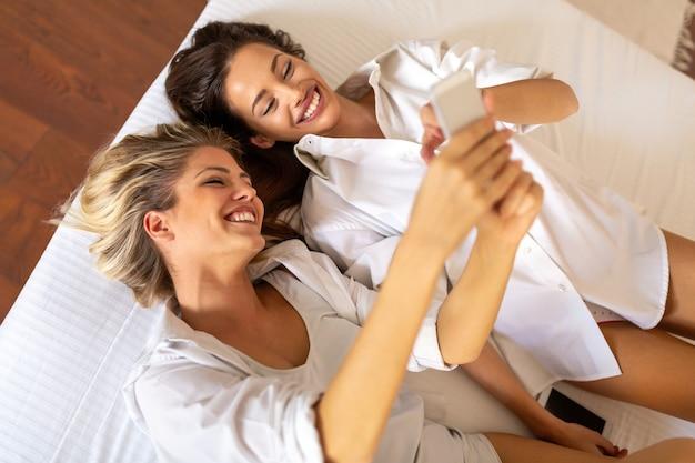 Счастливая пара лесбиянок, друг женщин весело с мобильным телефоном. люди, технологическая концепция
