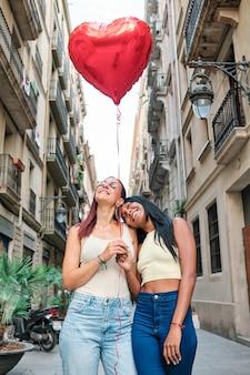 야외 거리에 서 있는 동안 하트 모양의 풍선을 들고 행복 한 레즈비언 커플. lgbt 개념입니다.