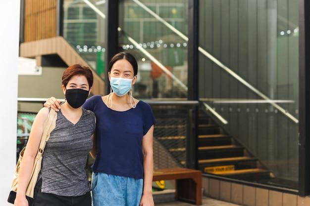 建物の前でお互いを抱きしめる保護マスクで幸せなレズビアンのカップル