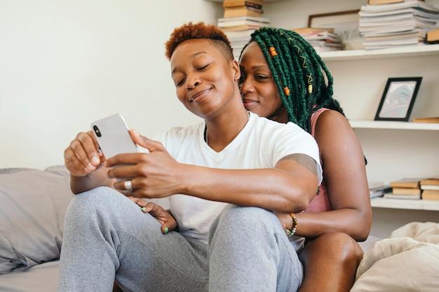 Счастливая пара лесбиянок играет по телефону