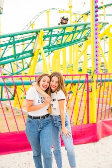 Happy lesbian couple standing in front of roller coaster ride
