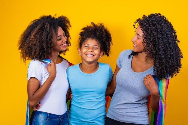 Счастливая пара лесбиянок с ребенком на желтом фоне. пара вместе с приемной дочерью, концепция усыновления