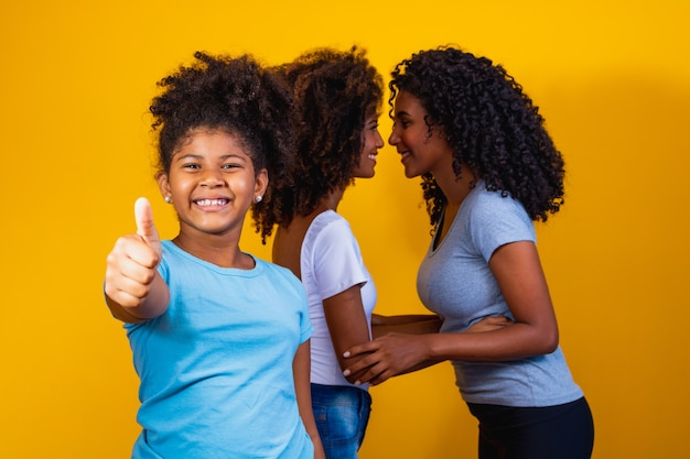 Happy lesbian couple with child on yellow background. couple together with adoptive daughter, adoption concept