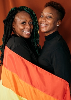 Happy lesbian couple with a colorful flag