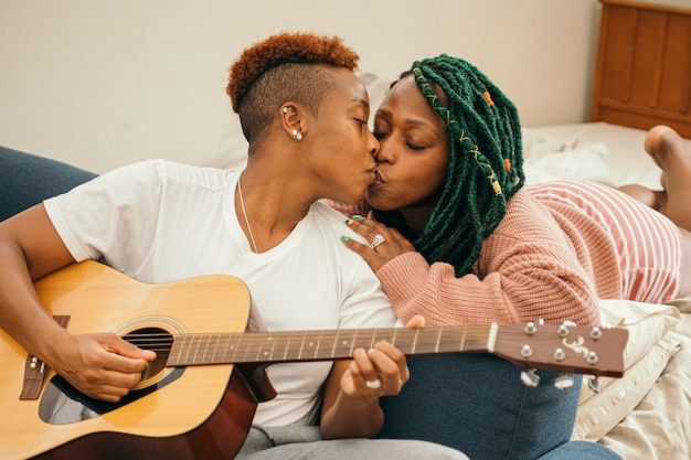 Happy lesbian couple with a guitar kissing
