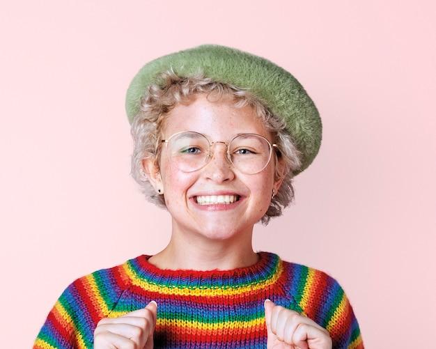 ピンクの壁のモックアップに虹のセーターと幸せなレズビアンの女性