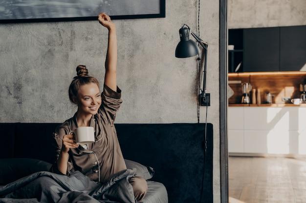 幸せな生活。目を覚ました後、ベッドで朝のコーヒーを飲み、サテンのパジャマを着て、手を伸ばして、週末に家でリラックスしながら新しい日を楽しんでいる魅力的な若い幸せな女性