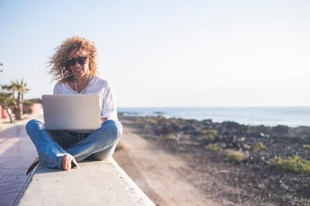 幸せなライフスタイルデジタル遊牧民の若い陽気な女性はラップトップコンピューターで屋外で働く